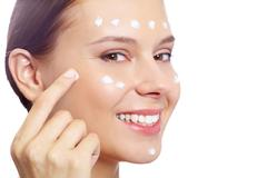 Fresh woman applying hydrating cream onto her face Stock Photos