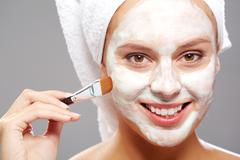 fresh woman applying facial mask onto her face with brush - stock photo