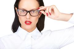 Stock Photo of gorgeous woman with red lips touching eyeglasses while looking at camera
