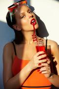 Gorgeous woman with glass of juice in swimming pool Stock Photos