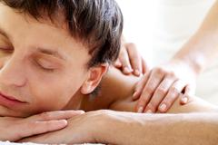 portrait of calm guy enjoying the procedure of massage - stock photo