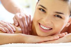 smiling female looking at camera during luxurious procedure of massage - stock photo