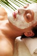 young man having pore cleaning procedure in parlor - stock photo
