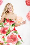 Happy woman in glamorous dress with floral print looking at camera Stock Photos