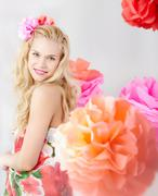 happy woman with pink flower in wavy hair looking at camera - stock photo