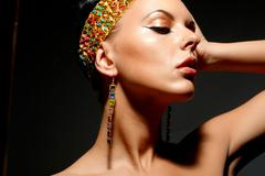 Gorgeous woman with exotic accessories on black background Stock Photos