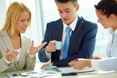 group of business partners sitting and planning work - stock photo