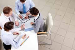 above view of four businesspeople discussing documents - stock photo