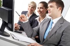 portrait of friendly workteam looking at while confident businessman pointing at - stock photo