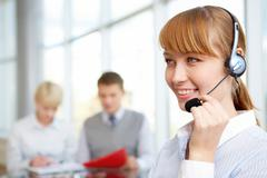 Young female wearing headset and speaking to clients with team of partners worki Stock Photos