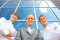 below angle of three successful partners looking at camera with smiles - stock photo