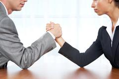 portrait of business competitors doing arm wrestling and looking into each other - stock photo