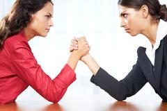 Profile of two women in struggle while their arms being wrestled Stock Photos