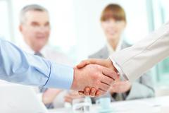 Photo of handshake of business partners on background of two partners applauding Stock Photos
