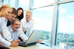 Photo of happy co-workers planning work while looking at laptop screen Stock Photos