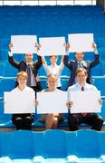 Stock Photo of portrait of several successful partners with blank papers sitting on stadium and