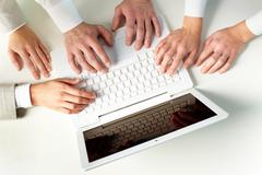 Human hands on keypad of laptop at workplace Stock Photos