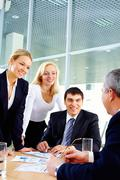 three businesspeople looking at their boss - stock photo