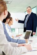 Senior business man showing something on a whiteboard to his colleagues Stock Photos