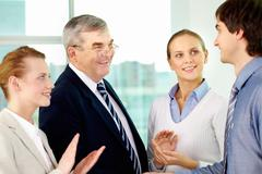 photo of successful businessmen handshaking after striking deal with applauding - stock photo