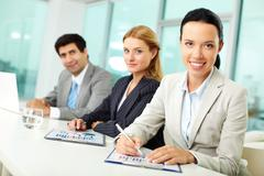 portrait of young woman and her colleagues at workplace looking at camera and sm - stock photo