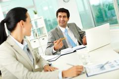 confident businessman explaining his ideas to colleague at meeting - stock photo