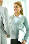 portrait of happy businesswoman shaking hands with partner at meeting - stock photo