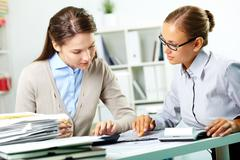 portrait of young businesswomen working with papers in office - stock photo
