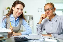 Portrait of happy young businesswomen looking at camera in office Stock Photos