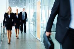 business people walking along the office corridor - stock photo