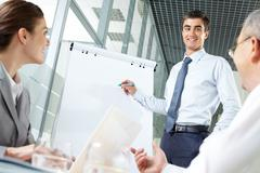 Smiling business man presenting new project to his partners on a whiteboard Stock Photos