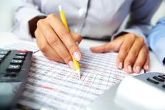 Photo of human hands holding pencil and marking numbers in documents Stock Photos