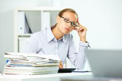 portrait of smart businesswoman thinking at work in office - stock photo