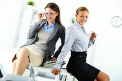 Portrait of happy young businesswomen posing in office Stock Photos