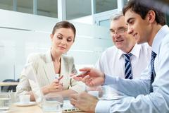 A business team of three sitting in office and planning work Stock Photos