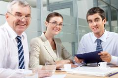 Smiling business partners looking at camera in office Stock Photos