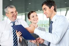 Smiling man explaining business document while his partners looking at him Stock Photos