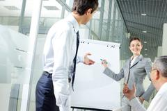 Stock Photo of image of young woman explaining ideas on whiteboard at meeting