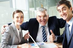 Portrait of joyful business group showing their gladness and looking at camera Stock Photos