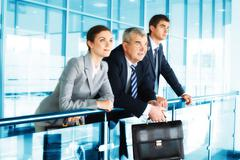 three business people in office looking at one point - stock photo