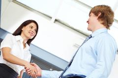 Successful business partners handshaking and looking at each other Stock Photos