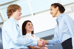 Image of business partners making an agreement with woman standing near by Stock Photos