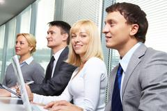 four business people working at conference - stock photo