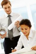 portrait of pretty businesswoman reading document with her boss at background - stock photo