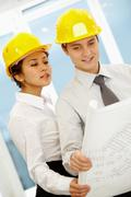 portrait of two architects in helmets looking at document at meeting - stock photo