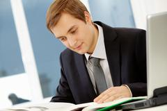 Portrait of thinking businessman reading book Stock Photos