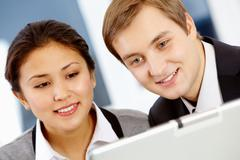 successful colleagues looking at laptop monitor with smiles during work - stock photo