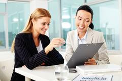 portrait of two young women at workplace discussing plan of work - stock photo