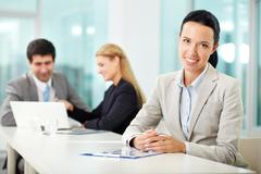 Stock Photo of portrait of a young woman at workplace looking at camera and smiling