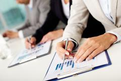 Image of female hands with pen over business document in working environment Stock Photos